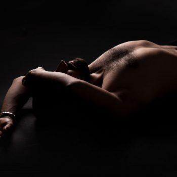 Hautnah Tantra Ulm Masseur Sharif liegt mit nacktem Oberkörper