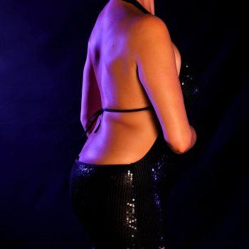 Hautnah Tantra Masseurin Alessa im schwarzen knappen Kleid und nacktem Rücken