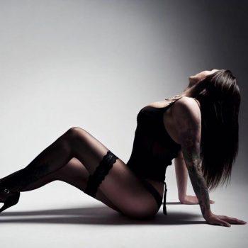 Hautnah Tantra Masseurin Marie in sexy schwarzem Slip und Top, tätowiert am Arm